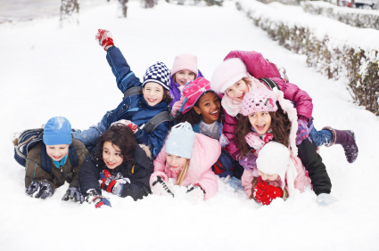 Funny group of children are lying in the snow.